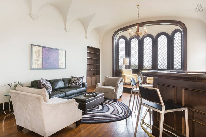 this-living-room-with-a-bar-and-large-bay-window-is-perfect-for-party-hosting
