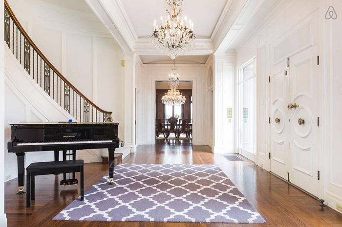 when-you-come-in-the-front-door-youre-greeted-by-an-enormous-winding-staircase-a-chandelier-and-a-piano-for-entertainment
