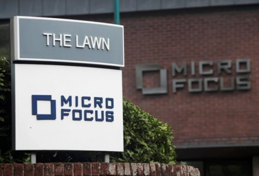 Signs stand outside the offices of Micro Focus in Newbury