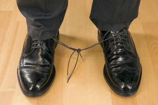 Business man with knotted laces