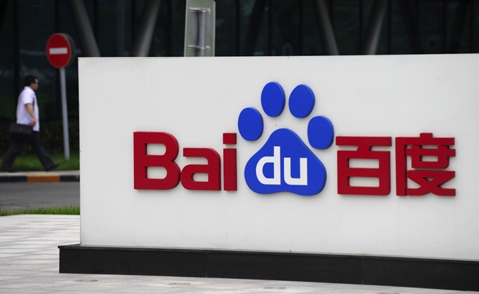 A man walks past the logo of Baidu at it