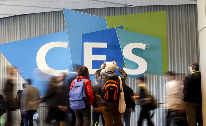 A couple takes a photo of the CES logo during the 2016 CES trade show in Las Vegas