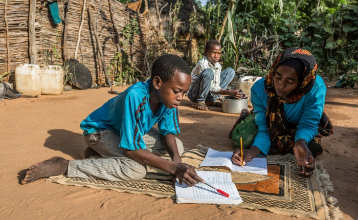 Chad. Refugee mother and her children study together